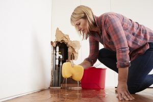 woman-sponging-up-water-from-burst-pipe