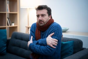 man-shivering-in-home-with-sweater-and-scarf-on
